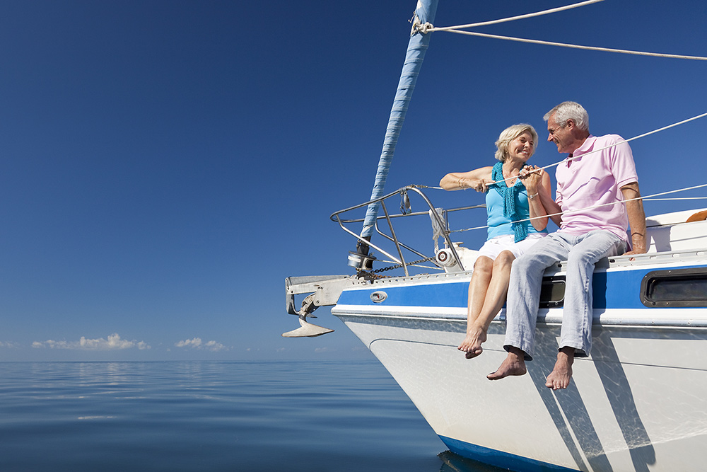 Elderly couple relaxing on sailing yacht holding hands